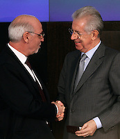 Il Presidente dell'Ordine dei Giornalisti Enzo Iacopino cinsegna la tessera di giornalista al Presidente del Consiglio Mario Monti, a destra, all'inizio della conferenza stampa di fine anno a Roma, 29 dicembre 2011..Italian Journalists Order's president Enzo Iacopino gives the new journalist card to Premier Mario Monti, right, during the year-end press conference in Rome, 29 december 2011..UPDATE IMAGES PRESS/Riccardo De Luca