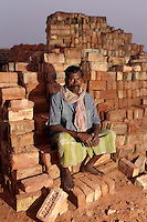 A worker sits in a brick-making factory on the outskirts of Kolkata, India. November, 2013