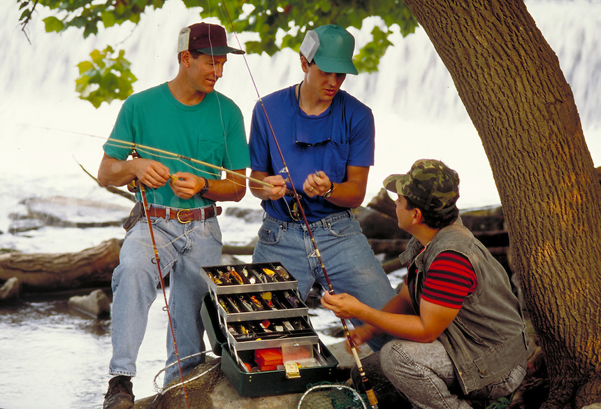 two young adult caucasian men and one young adult hispanic man choose flies for flyfishing. three men. New Cumberland Pennsylvania United States Yellow Breeches Creek.