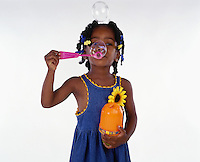 Girl blowing bubbles. Black girl blowing bubbles. Young girl blowing bubbles.