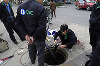 A China NetCom (CNC) workers repair telephone lines outside a manhole on a Beijing, China street..