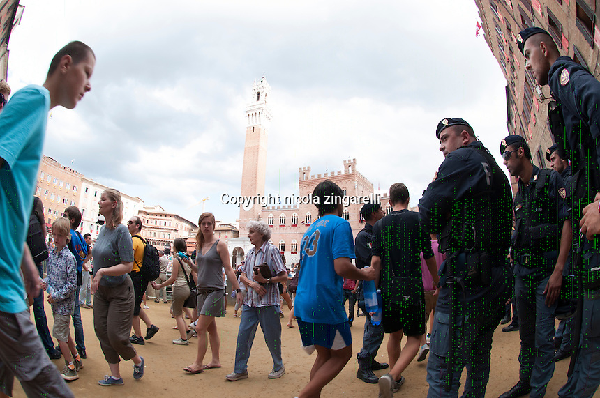 people slowly gathering inside the piazza del campo before the start of the palio di siena, the police keep an eye on the crowd