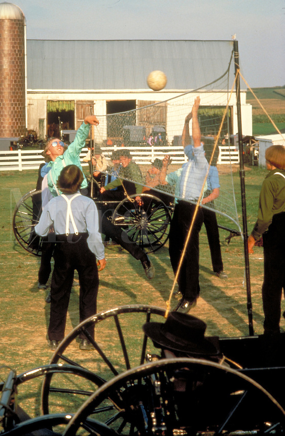 Amish teen boys play volleyball on a farm at a buddy group social using buggy wheels to hold net posts. Amish teens. Lancaster Pennsylvania United States farm.