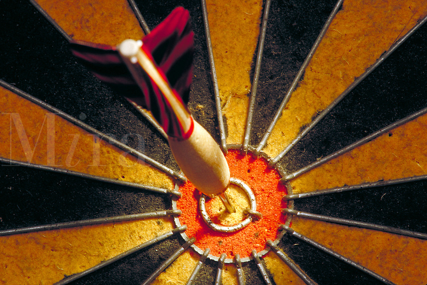 Dart in bulls eye of a dart board.