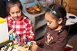 Education Preschool two girls playing together with small human figures talking pretend play lining them up in row