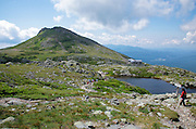 Hikers pass Lakes of the Clouds along the Appalachian Trail (Crawford Path) in the White Mountains, New Hampshire. during the summer months. Mount Monroe and Lakes of the Clouds Hut is in view.