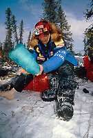 Martin Buser drains his boots at the Cripple checkpoint during the 1996 Iditarod Sled Dog Race, Interior Alaska, Winter