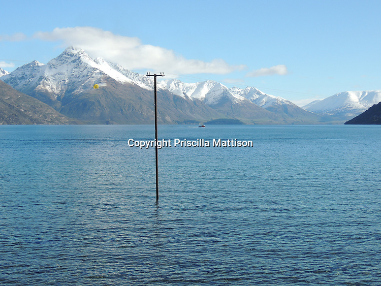 Queenstown, New Zealand - September 12, 2012:  A utility pole is reflected in the waters of Lake Wakatipu.  In the distance, a boat tows a yellow parasail.