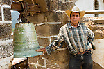 Portrait of Guatemalan man with cowboy hat in front of church bell in San Juan La Laguna, Lake Atitlan, Guatemala