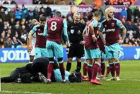 Winston Reid of West Ham is being seen to by medical staff after getting injured during the Premier League match between Swansea City and West Ham United at The Liberty Stadium, Swansea, Wales, UK. Saturday 03 March 2018