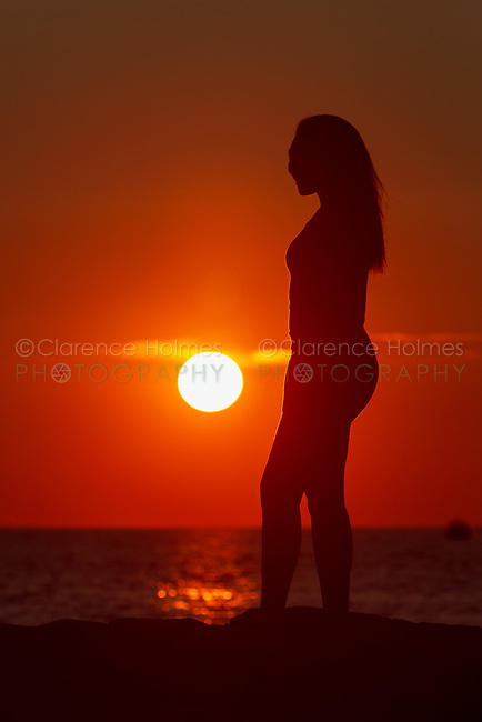 A woman is silhouetted by the sun as the sun sets over the Vineyard Sound at Menemsha Beach in Chilmark, Massachusetts on Martha's Vineyard.