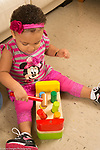 18 month old toddler girl at home, using mallet to hit cobbler's bench toy (pushing down pegs)