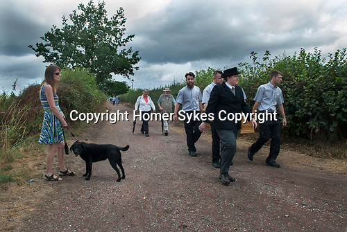 Brinsley Coffin Walk to Greasley Church, Nottinghamshire 2018. Joanne Hutsby from Gillotts Funeral Directors leads the walk from St James the Great Church built in1861.<br /> The walk has been taking place since 2004, in commemoration of the time when the people of Brinsley used to have to walk three miles to Greasley Church to bury their dead. A full size replica coffin is made by Steve Soult Ltd, coffin manufacturers and carried by members his staff. In 2018 the ceremony was in memory of local historian Doreen Lockett who had performed a symbolic service in St Mary's Church graveyard as part of the commemoration in previous years.