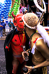 'GAYFEST MANCHESTER, UK', DRESSED AS A DEVIL AND AN ANGEL TWO MEN KISS EACH OTHER DURING THE PARADE, THROUGH MANCHESTER, 1999