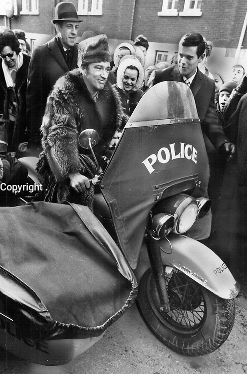 1969 FILE PHOTO - ARCHIVES -<br /> <br /> Whooping it up in his raccoon coat at the Quebec Winter Carnival, Prime Minister Pierre Trudeau rides a police motorcycle - one of a weird succession of parade vehicles he tried out to the delight of crowds during a fun weekend.<br /> <br /> PHOTO :  Jeff Goode - Toronto Star Archives - AQP