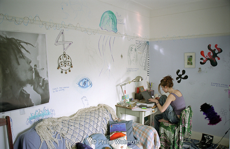 Teenager uses a laptop to do her homework in her bedroom.