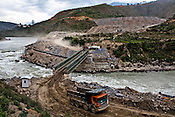 Trucks carry construction material over the Punatsangchu river at the Punatsangchu Hydro Power Project site in Punakha, Bhutan. Photo: Sanjit Das/Panos