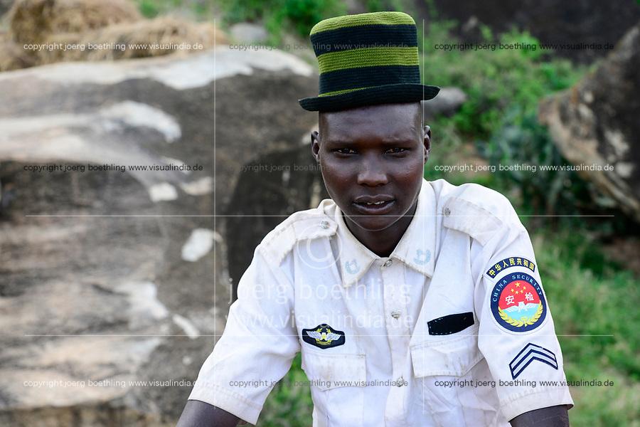 UGANDA, Karamoja, village Lokanayona, Karamojong tribe, young warrieor with woolen hat and shirt with textile sticker China Security