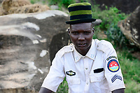 UGANDA, Karamoja, village Lokanayona, Karamojong tribe, young warrieor with woolen hat and shirt with textile sticker China Security