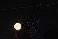 Pictured: The August full moon is seen rising over the Green Man statue. Sunday 22 August 2021<br /> Re: Green Man Festival near Crickhowell, Wales, UK.