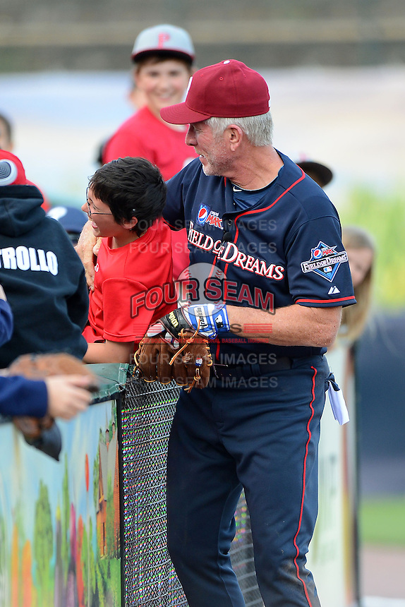 Hall of Fame third baseman Mike Schmidt #20 jokes with a young fan who he tossed the game ball to help him throw it back to the pitcher during the MLB Pepsi Max Field of Dreams game on May 18, 2013 at Frontier Field in Rochester, New York.  (Mike Janes/Four Seam Images)
