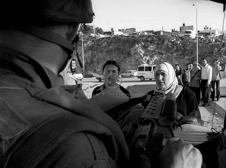 An Israeli soldier points a gun to a Palestinian woman as other Palestinians wait in a line form him to make ID checks at the Kalandia checkpoint April 11,2002. On the eve of U.S. Secretary of State Colin Powell's mission, Israeli troops remain in four West Bank towns.Photo by Quique Kierszenbaum