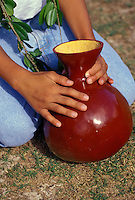 A ten year old child wearing maile taps an ipu (hollowed gourd), which keeps rhythm for hula dancers.