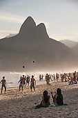 Rio de Janeiro, Brazil. Two girls talking and watching as people are kicking footballs in the air on Leblon beach with the Dois Irmaos mountain behind.