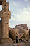 The shattered head and shoulders of the colossus of Ramses II and a Osiride column at the Ramesseum on the West bank of the River Nile at Thebes.The Ramesseum is the mortuary temple of Ramses II who ruled Egypt from 1279-1212 BC.Thebes is the name the Greeks gave to Waset, the ancient capital of Egypt.