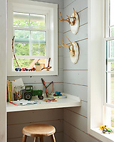 In the boys' bedroom, a table shelf set in a window recess provides a space for study.