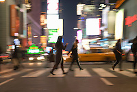 AVAILABLE FROM GETTY IMAGES FOR COMMERCIAL AND EDITORIAL LICENSING.   Please go to www.gettyimages.com and search for image # 135307808.<br /> <br /> Busy, Blurred Motion Scene of Two Young Women Crossing Street During the Evening Rush Hour with One Woman Reading Text Message on Her Cell Phone, Times Square and 42nd Street, Midtown Manhattan, New York City, New York State, USA