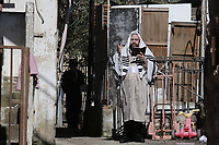 Un Haredi envuelto en su manto de rezo o talit, lidera el rezo matinal en un balcón del barrio ultra ortodoxo Mea Shearim.  Tras la decisión del gobierno de prohibir los rezos en sinagogas los haredis recibieron un permiso religioso para coordinar y llevar a cabo el rezo en los techos y balcones del barrio manteniendo el distanciamiento de 2 metros. Según las leyes religiosas para poder llevar a cabo un rezo en una sinagoga se necesita un mínimo de 10 hombres en el lugar. Para no romper esta regla los haredis tienen que ver en los balcones y patios aledaños un mínimo de diez hombres. <br /> En un esfuerzo por detener el contagio del COVID 19 el gobierno israelí decreto el uso obligatorio de barbijos en las calles. La pandemia ha afectado fuertemente a la comunidad Haredi. El gobierno israelí decreto un confinamiento limitando la salida a 100 metros de los hogares. <br /> Foto Quique Kierszenbaum