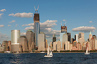 Sailboats catch the breeze on the Hudson River in New York City late on a summer afternoon, with the buildings of the World Financial Center and the World Trade Center complex, including the Freedom Tower (One World Trade Center), in the background.