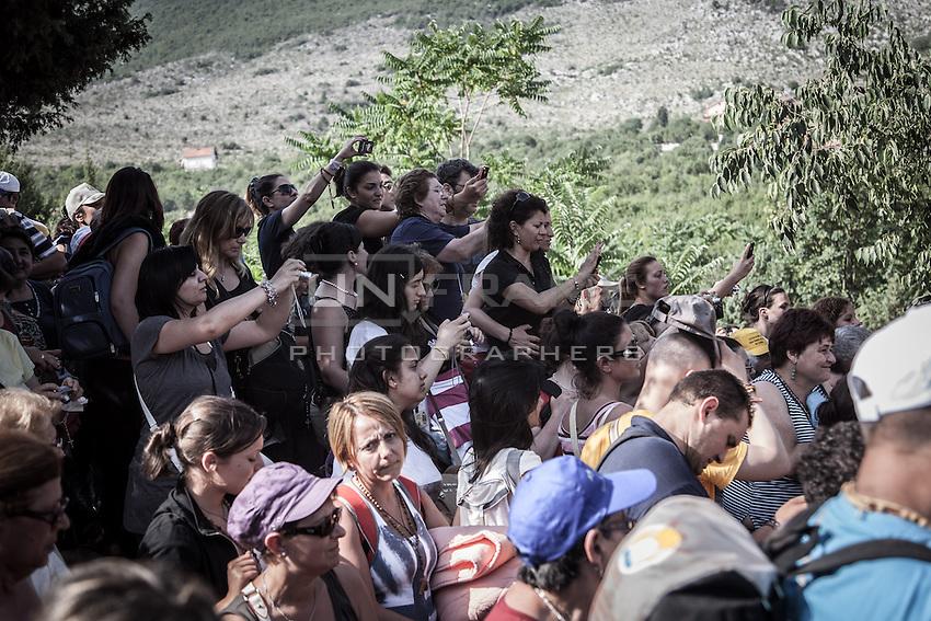 Pilgrims filming the visionary  Mirjana Dragicevic after the apparition  of July 2 at the Blue Cross, Podbro hill.  <br /> Bijakovici, Medjugorje, Bosnia and Herzegovina.