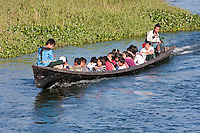 Myanmar, Burma.  School Children Riding  Home after School, Inle Lake, Shan State.  The school canoe rather than the school bus is the mode of transportation for these children living in the villages of Inle Lake.
