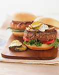 Two hamburgers on a wooden cutting board. Large beef patties with lettuce, tomato, grilled onion, mayonnaise, and pickle slices on white buns.