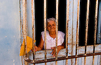 Portrait of old woman behind bars in front in Trinidad Cuba