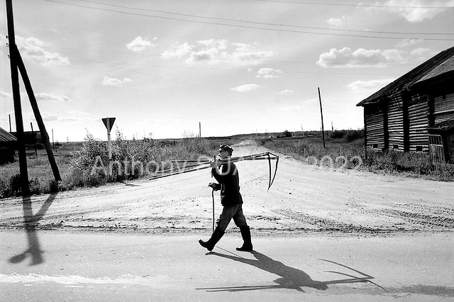 Averkievskaya, Russia  .1998.75 year old, Nickoli Kopietkov is the regions repair man for hand blade cutters used during the harvest season. He carries three home to his shop..
