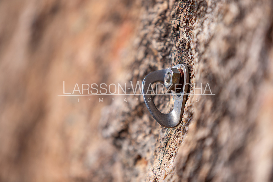 Closeup of rock climbing bolt placed into rock face in Parc Naturel Régional de Corse, Corsica, France
