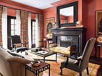 Chinese ancestor paintings are hung on walls lacquered in deep coral in the living room. A massive Flemish inspired custom fireplace, under an antique Dutch mirror, dominates the room. The bench is from John Boone, and the drapery fabric is Cowtan & Tout.