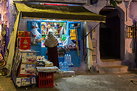 Chefchaouen, Morocco.  Customer at Neighborhood Sundries Shop in the Medina at Night.