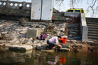 CHINA. Jiangxi Province. Jiujiang. A woman cleans clothes in a lake in the entre of the city. Jiujiang is a city of 4.6 million people, located on the southern shore of the Yangtze River.  2008