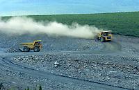 Billowing dust follows a dump truck in a quarry.