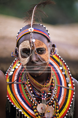 Lolgorian, Kenya. Siria Maasai Manyatta; woman with white and red ochre face paint, brightly coloured beadwork adornments. earrings and bracelets.