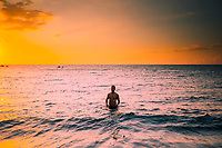 A man enjoys the glow of the sunset on the ocean while camping at a beach in Kailua-Kona, Hawai'i Island.