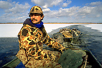 A male hunter in camouflage clothing hauls decoys through icy water in a duck boat.