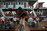 A labourer unloads a box from a passenger ferry at the Rangoon (Yangon) River docks.