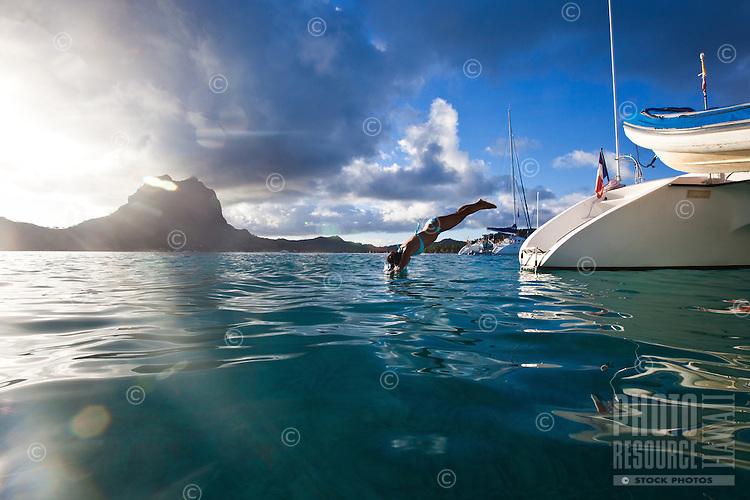 Woman diving off stern of catamaran in Bora Bora's lagoon