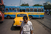 A pedestrians crosses the street while a bus reverses at a busy intersection in Kolkata, West Bengal, India.