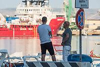 """Im Hafen der Sizilianischen Kleinstadt Porto Empedocle wurden die Rettungsschiffe """"Sea-Watch 3"""" und """"Ocean Viking"""" der privaten Seenotrettungsorganisationen Sea-Watch und SOS Mediterranee, von der italienische Küstenwache im Juli 2020 festgesetzt. Zuvor hatten die Organisationen mit den beiden Schiffen mehrere hundert Menschen vor der libyschen Kueste aus Seenot gerettet. Die italienischen Behoerden versuchen mit der offiziellen Begruendung, """"Sicherheitsmaengel"""", weitere Rettungseinsaetze zu blockieren.<br /> Im Bild: Passanten betrachten die Ocean Viking.<br /> 25.7.2020, Porto Empedocle<br /> Copyright: Christian-Ditsch.de<br /> NUR FUER REDAKTIONELLE ZWECKE! Werbung nur auf Anfrage beim Fotografen. [Inhaltsveraendernde Manipulation des Fotos nur nach ausdruecklicher Genehmigung des Fotografen. Vereinbarungen ueber Abtretung von Persoenlichkeitsrechten/Model Release der abgebildeten Person/Personen liegen nicht vor. NO MODEL RELEASE! Don't publish without copyright Christian-Ditsch.de, Veroeffentlichung nur mit Fotografennennung, sowie gegen Honorar, MwSt. und Beleg. Konto: I N G - D i B a, IBAN DE58500105175400192269, BIC INGDDEFFXXX, Kontakt: post@christian-ditsch.de<br /> Bei der Bearbeitung der Dateiinformationen darf die Urheberkennzeichnung in den EXIF- und  IPTC-Daten nicht entfernt werden, diese sind in digitalen Medien nach §95c UrhG rechtlich geschuetzt. Der Urhebervermerk wird gemaess §13 UrhG verlangt.]"""